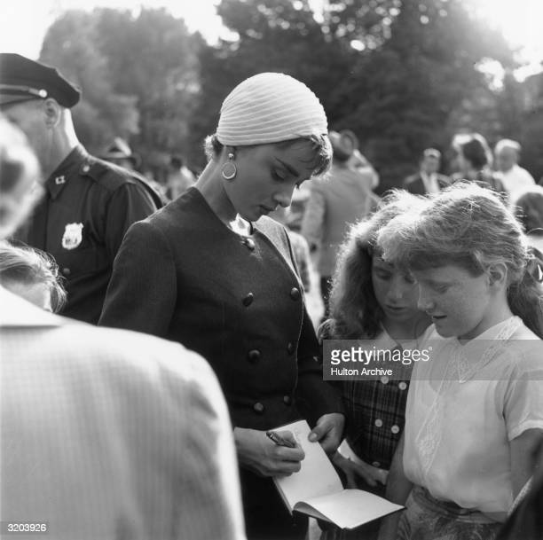 Belgian-born actor Audrey Hepburn signs an autograph book for two young girls on the set of director Billy Wilder's film, 'Sabrina'. Hepburn wears a...