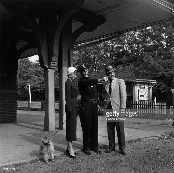Fulllength image of Belgianborn actor Audrey Hepburn holding a poodle on a leash and American actor William Holden taking directions from a police...