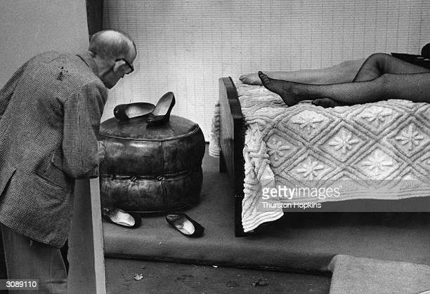 Two programme sellers at the National Leather Week exhibition site kick off their leather shoes and take a wellneeded rest Original Publication...