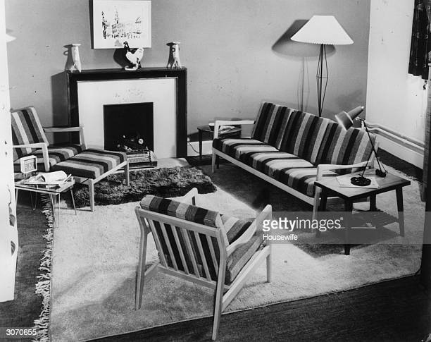 A Danish designed suite of furniture with wooden arms and covered with a striped wool fabric Housewife A Room To Relax In pub 1955