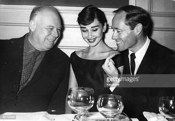 Belgian born British actress of AngloDutch descent Audrey Hepburn t in a Paris restaurant with actor Mel Ferrer and film director Jean Renoir