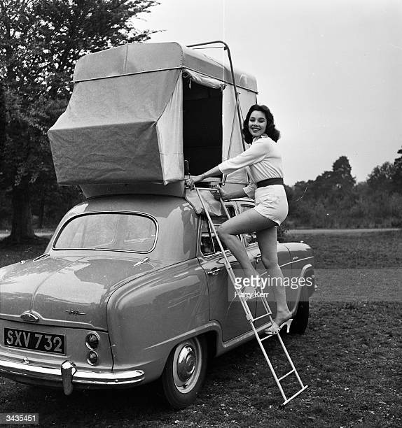 British actress and model Marigold Russell demonstrates the 'Roofsleeper' a car tent mounted on a plinth shaped to suit the contours of a car roof...
