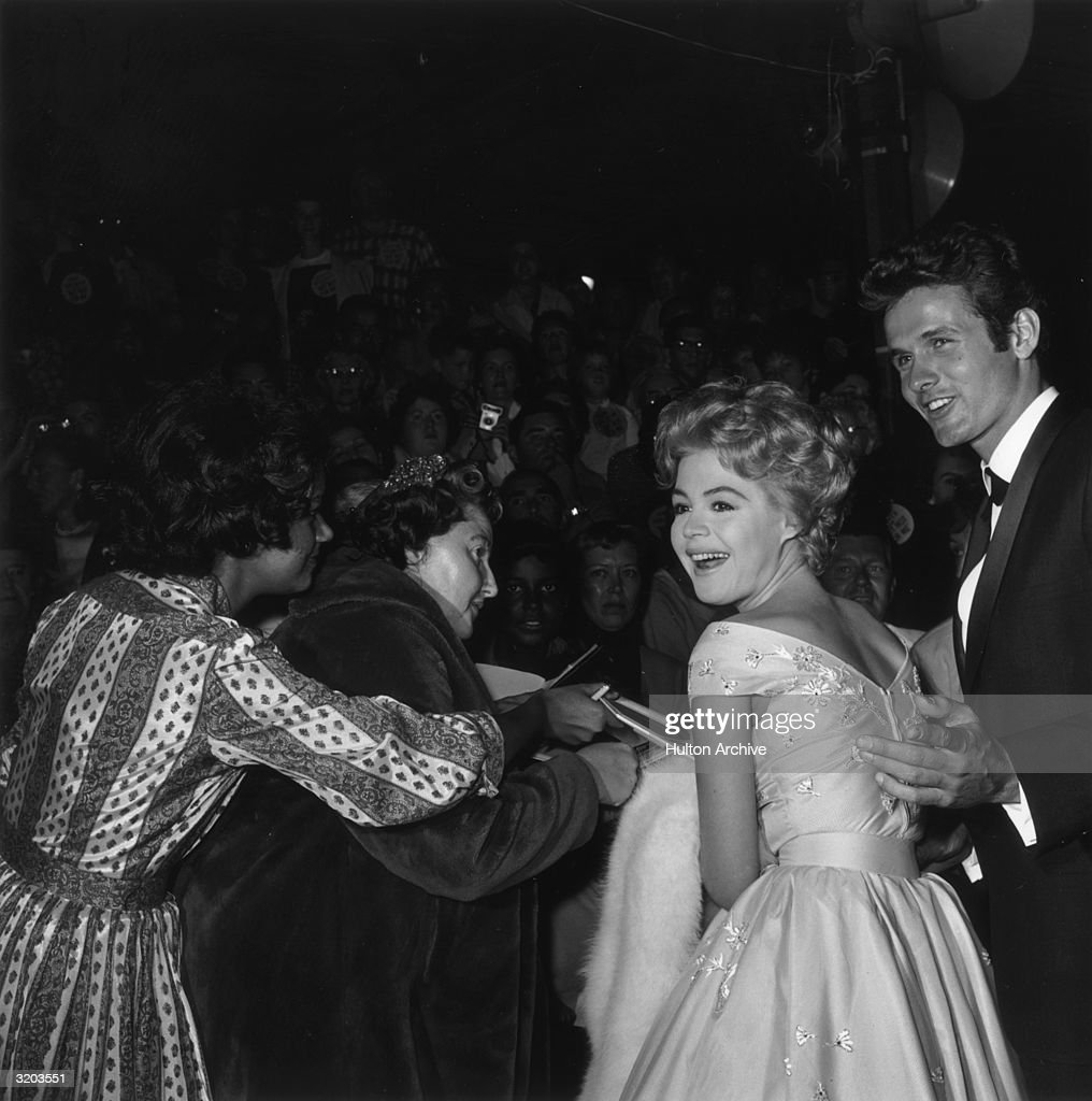 American actor Sandra Dee and her date, Mark Goddard, look over their shoulders during an autograph signing for crowds gathered at the premiere of director Walter Lang's film, 'But Not For Me', Pantages Theater, Hollywood, California. Dee is wearing a dress embroidered with flowers while holding a white fur wrap.