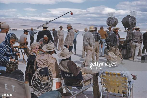 American film star Marilyn Monroe sitting with her costars during the location filming of 'The Misfits' in Nevada