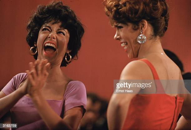 Rita Moreno shares a joke with a costar on the set of the musical 'West Side Story' directed by Robert Wise and Jerome Robbins