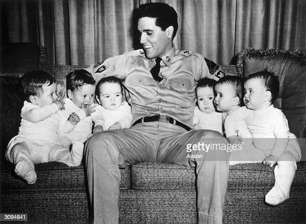 Rock 'n' roll singer Elvis Presley with six babies during the making of the film 'GI Blues' in which he plays a soldier Due to employment laws in...