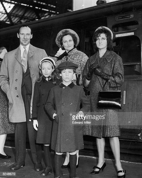 The newlyknighted Sir David OrmsbyGore British Ambassador to the US leaves Victoria Station en route to the States With him are his wife Sylvia and...
