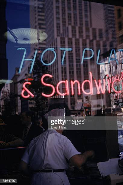 A chef at work under a neon sign in a window advertising 'Hot Plates and Sandwiches'