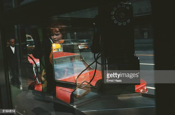 A New York street seen through and reflected in the windows of a phone booth