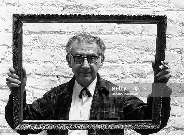 Painter, photographer and film-maker Man Ray peering through a picture frame which he is holding up as he stands against a whitewashed wall.