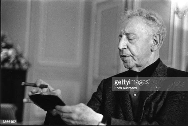 Polish-born US pianist Arthur Rubinstein smoking a cigar at the Savoy Hotel, London.
