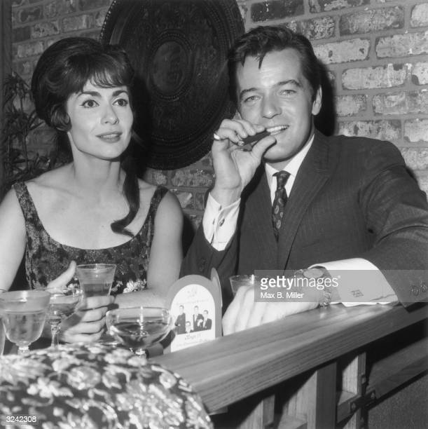 American actor and singer Robert Goulet and his wife, actor and singer Carol Lawrence, sitting at a table at the Vic Damone opening at Century Plaza,...