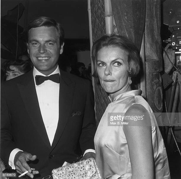 American actor Robert Wagner wearing a tuxedo and holding a cigarette smiles and stands beside his second wife actor Marion Marshall at the premiere...