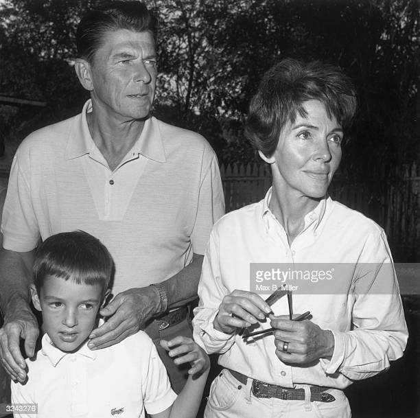 California governor Ronald Reagan and his wife Nancy stand outdoors with their young son Ron Reagan Jnr