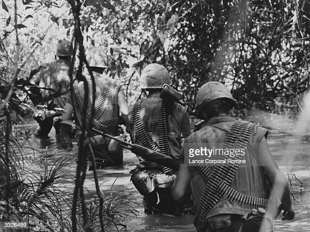 Five team members of F Company, 2nd Battalion, 5th Regiment, US Army, wade through a waist-deep stream, roofed over by dense jungle, about 400 metres...