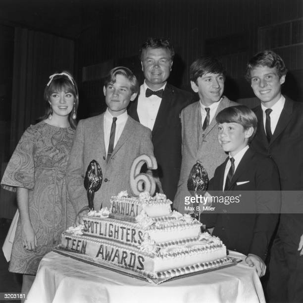 LR Actors Veronica Cartwright Kurt Russell unidentified man Bob Denver Bill Mumy and Jay Noan pose for a picture behind a threetier cake at the sixth...