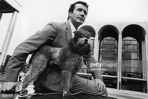 Portrait of Italian opera singer Franco Corelli posing with his poodle in front of the Metropolitan Opera at Lincoln Center in New York City.