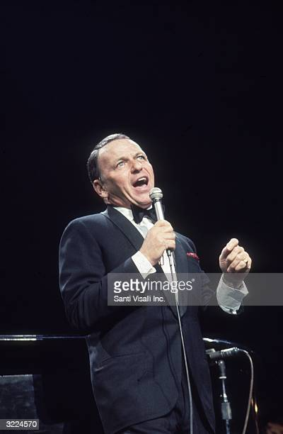 American singer and actor Frank Sinatra wearing a tuxedo with a red handkerchief in the pocket singing with his mouth wide open at antidefamation...