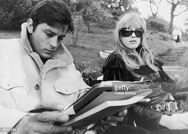 French actor Alain Delon reads a script as he sits on a park bench with British singer and actor Marianne Faithfull who is wearing a leather outfit...