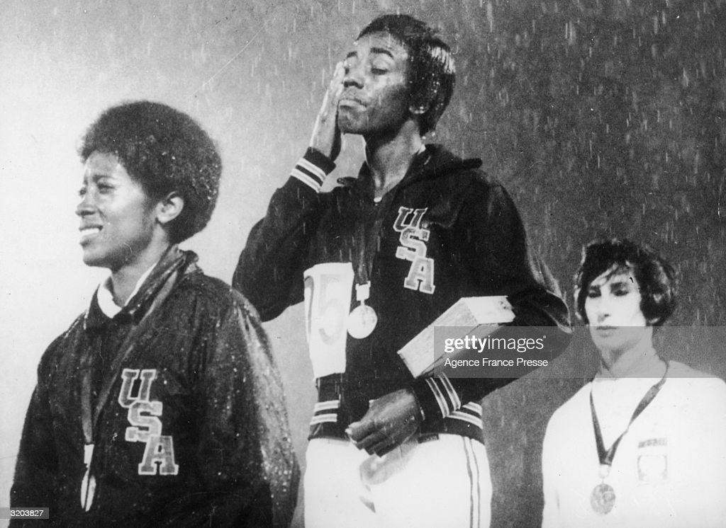American athlete Wyomia Tyus (C) wipes rain from her cheek during the 100 meter event medal ceremony at the Summer Olympic Games, Mexico City, Mexico, 1968. Tyus won gold while American runner Barbara Ferewell (L) won silver and Polish runner Irene Szewinski won bronze.