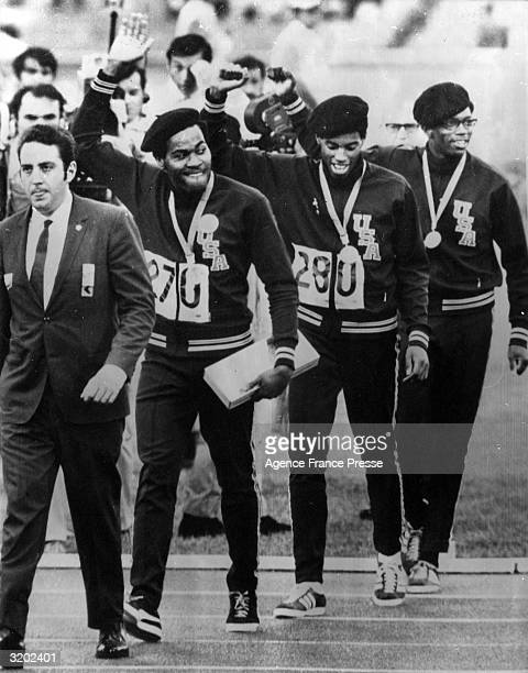 American runners Lee Evans, Larry James and Ronnie Freeman hold their hands up in a Black Power salute while walking with an escort after the medal...