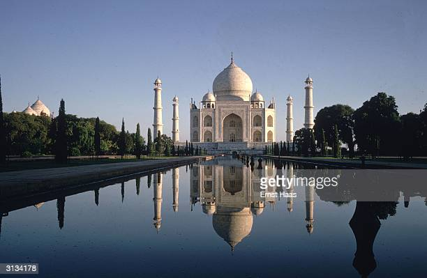 The Taj Mahal the trees of the great garden and a clear blue sky reflected in the lake at Agra Northern India