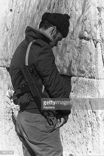 An Israeli soldier prays before the Western or Wailing Wall