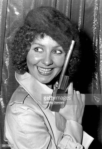 British pop singer Lulu posing with the gun from the James Bond film 'The Man With The Golden Gun' after being signed to sing the film's title song