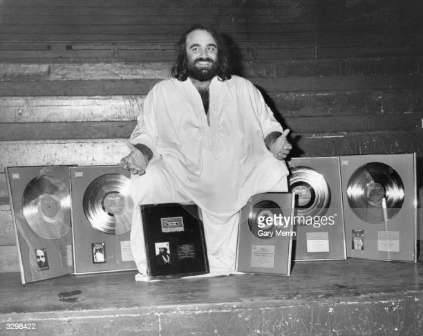 International singing star Demis Roussos surrounded by awards for the UK sales of his albums a silver disc for 'Fire And Ice' gold discs for 'Happy...
