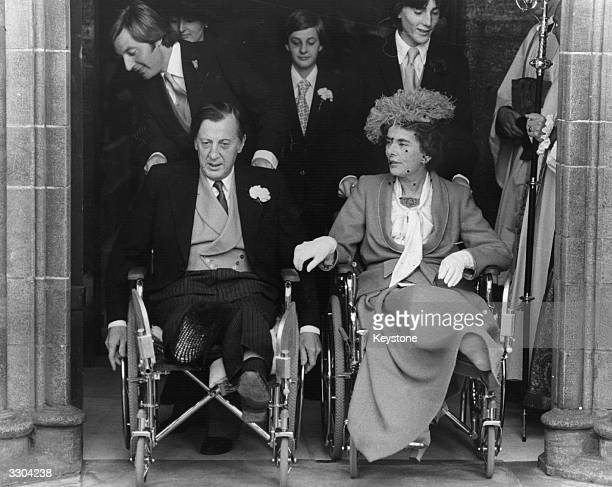 Lord Brabourne and his wife Countess Mountbatten of Burma being pushed by aides from Romsey Hants following the wedding of their son Lord Romsey to...