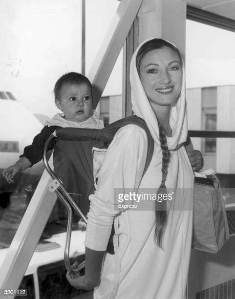 British actor Jane Seymour smiling over her shoulder as she carries her daughter Katie on her back through Heathrow Airport London England Seymour is...