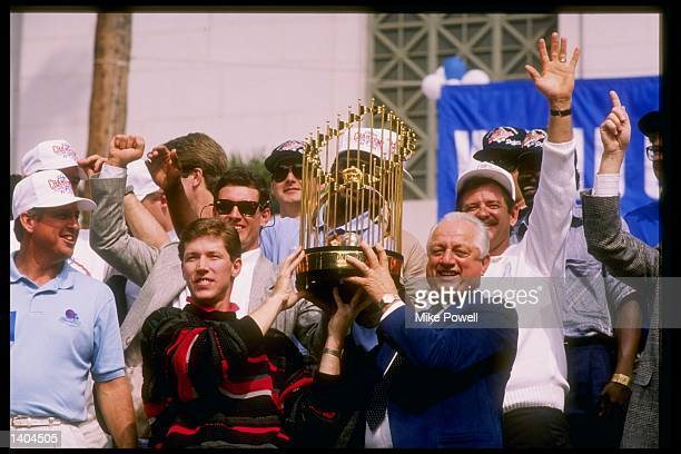 Pitcher and World Series MVP Orel Hershiser and manager Tommy Lasorda of the Los Angeles Dodgers hold up the World Series trophy in front of a crowd...