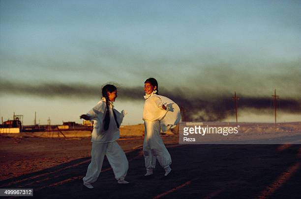 October 1997 Caspian Sea Chelikan Peninsula Turkmenistan Two young girls from a folklore troupe dancing while polluting waste looms on the horizon