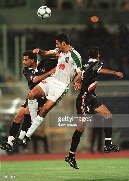 Ali Daei of Iran clashes with Husham M Fiead and Abdul Jabar Hanon of Iraq during the 10 Iran win over Irag yesterday at the Saida Stadium Saida...