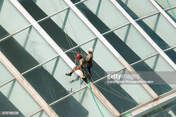 14 October 2009 Valencia Spain Maintenance workers equipped with climbing gear are cleaning the glass facade of the Hemisferic The Building is part...