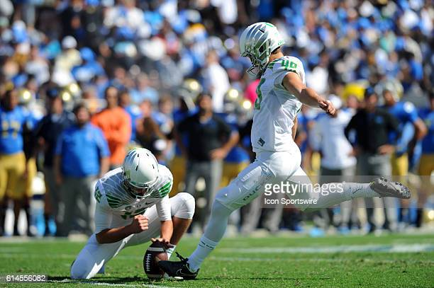 Oregon Taylor Allie holds the ball as Oregon Matt Wogan kicks the extra point during an NCAA football game between the Oregon Ducks and the UCLA...