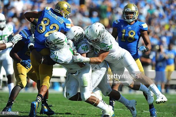 UCLA Eldridge Massington is taken down by Oregon Erick Dargan Rodney Hardrick and Joe Walker during an NCAA football game between the Oregon Ducks...