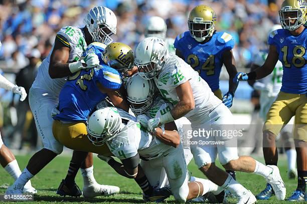 UCLA Eldridge Massington is taken down by Oregon TJ Daniel Erick Dargan Rodney Hardrick and Joe Walker during an NCAA football game between the...