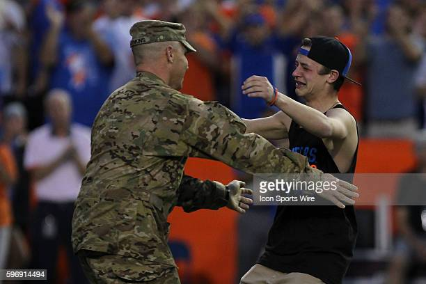 Chief Warrant Officer Kristian Denkins runs to his son a he surprises his family after returning home from duty during the NCAA football game between...