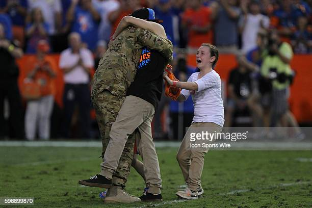 Chief Warrant Officer Kristian Denkins surprises his family after returning home from duty during the NCAA football game between the Mississippi...