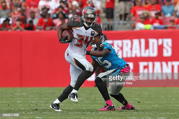 Tampa Bay Buccaneers running back Charles Sims runs thru a tackle attempt by Carolina Panthers cornerback Bene' Benwikere during the NFL Week 4 game...