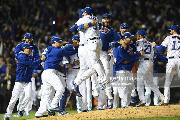 Chicago Cubs third baseman Javier Baez jumps with his team while celebrating after their victory for the National League Championship between the Los...