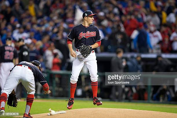 Cleveland Indians Shortstop Francisco Lindor bends down to use the rosin bag as Cleveland Indians Starting pitcher Trevor Bauer prepares to fire a...