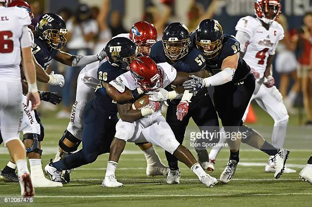 FIU safety Shermarke Spence linebacker Treyvon Williams and defensive end Newton Salisbury combine to stop running back Devin Singletary in the...
