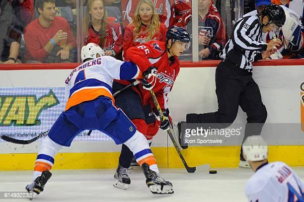 Washington Capitals left wing Andre Burakovsky controls the puck against New York Islanders defenseman Dennis Seidenberg as linesman Steve Barton...