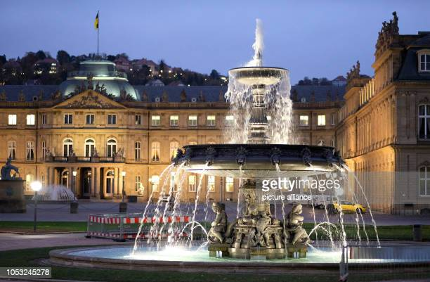 October 2018, Baden-Wuerttemberg, Stuttgart: In the early morning light the illuminated historical fountains on the Schlossplatz in front of the New...