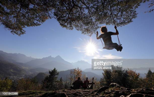 10 October 2018 Germany Berchtesgaden A woman sits on a swing on the Marxenhoehe in the Berchtesgadener Land and enjoys the warm rays of the October...