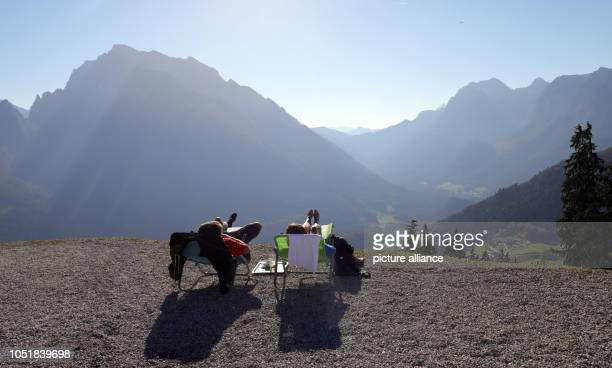 10 October 2018 Germany Berchtesgaden Mountain hikers lie in deck chairs on the 1400 metre high viewing platform of the Hirschkaser restaurant in...
