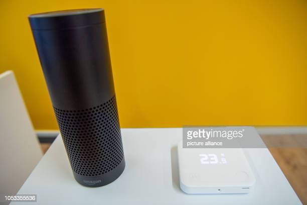 A smart thermostat of the heating network Startup Tado is located in the headquarters on a table next to Amazon's talking loudspeaker with assistant...
