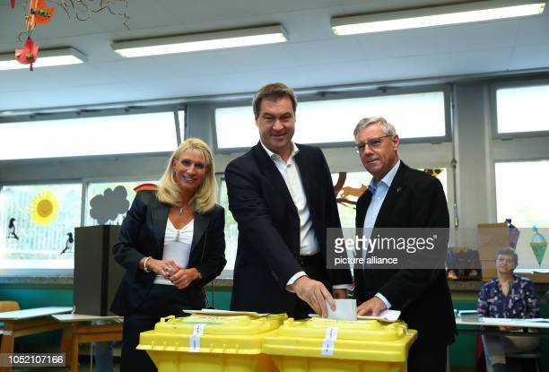 Prime Minister Markus Söder and his wife Karin cast their votes for the state elections in Bavaria On the right Wolfram Gäbisch the election leader...